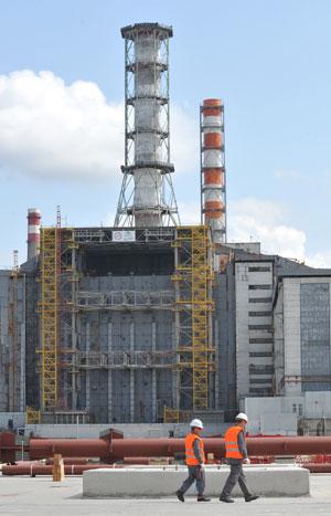 Trabalhadores caminham em frente à obra da nova estrutura de proteção em Chernobyl (Foto: Genya Savilov/AFP)