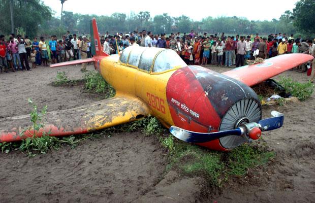Moradores cercam o avião bengali acidentado na manhã desta quinta-feira (26) (Foto: AFP)