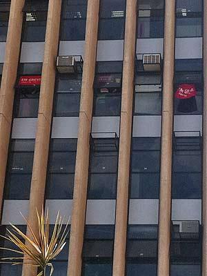 Bandeiras do sindicato dos professores em janelas do sexto andar da Secretaria de Administração do DF durante ocupação nesta quinta-feira (26) (Foto: Patrícia Alencar/G1)
