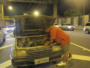 Fábio dos Santos tenta consertar o carro, enquanto aguarda o reboque (Foto: Tássia Thum/G1)