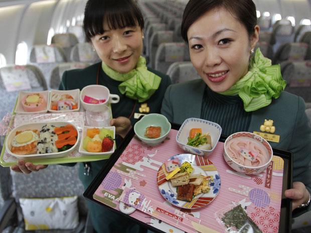 Aeromoças mostram pratos decorados a serem servidos durante o voo (Foto: Reuters)