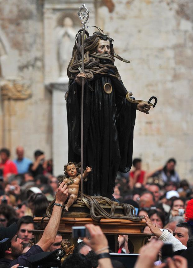 Multidão carrega a imagem de São Domingos coberta pelas cobras. O santo, que era frade do século X, é considerado curador de mordidas venenosas. (Foto: Tiziana Fabi/AFP)