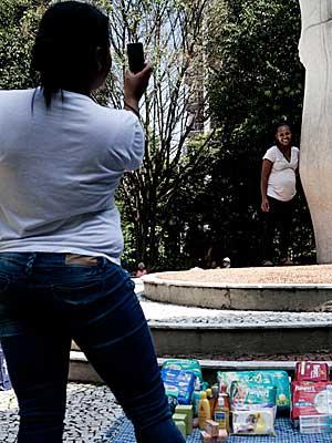 A babá Eliana Ferreira fotografa a colega Kelly, grávida que fez chá de bebê na praça Buenos Aires (Foto: Caio Kenji/G1)