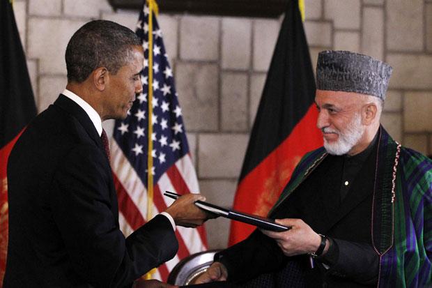 Obama e Karzai trocam os documentos assinados em Cabul (Foto: Charles Dharapak/AP)
