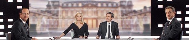 O socialista François Hollande  e o presidente Nicolas Sarkozy, nos cantos, antes do início do debate desta quarta-feira (2) (Foto: AFP)