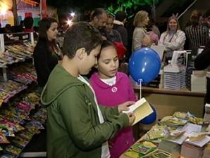 Crianças procuram livros em prateleiras no festival literário (Foto: Reprodução / TV Tem)