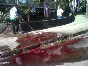 Homem limpa mancha de sangue, após assassinato na Barra (Foto: Carolina Lauriano/G1)