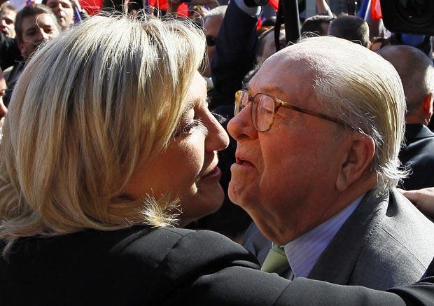A candidata derrotada da Frente Nacional à eleição presidencial francesa, Marine Le Pen, beija seu pai, Jean Marie, fundador do partido, em cerimônia nesta terça-feira pelo Dia dos Trabalhadores em Paris (Foto: AP)