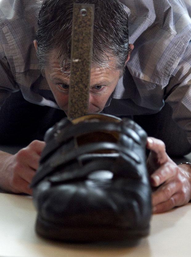 Técnico de calçados Paul Robinson tira medidas para o novo tênis (Foto: Steven Senne/AP)