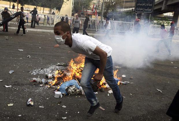 Manifestante foge de bomba de gás jogada pelas forças de segurança durante protesto nesta sexta-feira (4) no Cairo (Foto: Reuters)