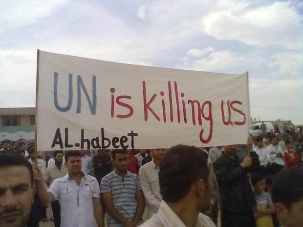 Manifestantes em Al-Habeet, na província síria de Idlib, protestam nesta sexta-feira (4) contra o governo Assad e contra a suposta inoperância da ONU na região. O cartaz diz: 'a ONU está nos matando' (Foto: AP)