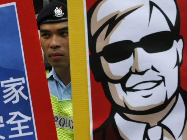 Protesto em Hong Kong, um policial é visto entre cartazes durante manifestação por Chen Guangcheng. (Foto: Vincent Yu / AP Photo)