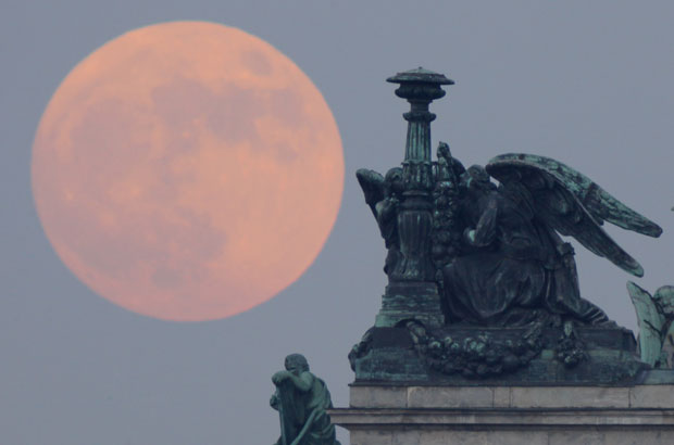 A lua cheia aparece por trás de estátuas na Catedral de Santo Isaac, em São Petersburgo, na Rússia, no início da noite deste sábado (5). Veja a explicação sobre a superlua no blog Observatório (acesse aqui). (Foto: Dmitry Lovetsky/AP)