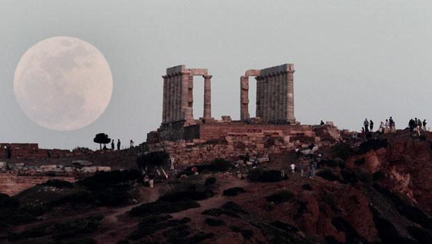 Turistas observam a lua surgir por trás do Templo de Poseidon, no Cabo Sounion, a sudeste de Atenas, na Grécia, neste sábado (5). (Foto: Dimitri Messinis/AP)