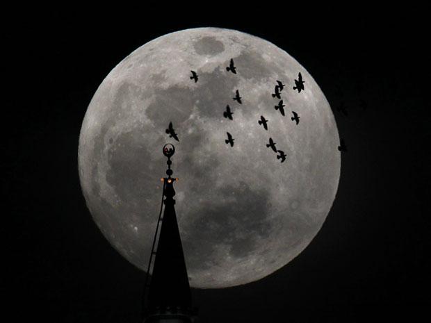 """Lua Cheia brilhante é clicada próxima a uma mesquita em Amman, na Jordânia, neste sábado (5). Na noite de hoje deve ocorrer o fenômeno chamado """"Superlua"""", no qual o astro aparecerá 14% maior e 30% mais brilhante do que nas outras Luas Cheias do ano. (Foto: Ali Jarekji/Reuters)"""