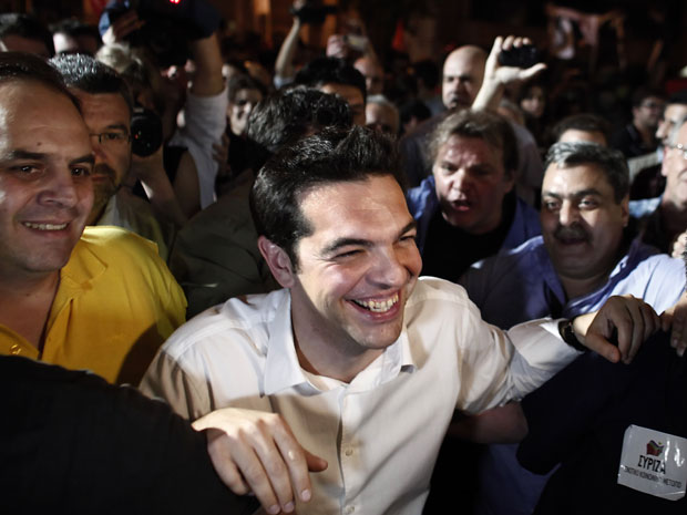 Líder do partido de coalizão Syriza, Alexis Tsipras sorri enquanto é acompanhado por partidários após eleições neste domingo (6) (Foto: AP Photo/Kostas Tsironis)