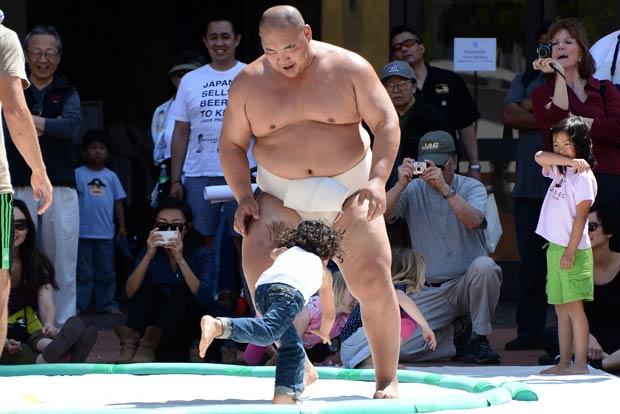 O tricampeão mundial de sumô Byamba ensina sua técnica a crianças nesta sexta-feira (5) em Los Angeles (Foto: AFP)