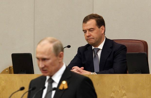 O presidente da Rússia, Vladimir Putin, fala ao parlamento, com o ex-presidente Dimitri Medvedev ao fundo (Foto: Reuters)