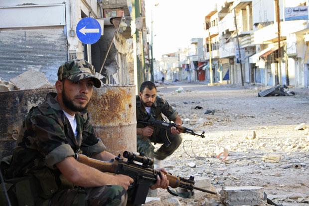 Soldados da oposição patrulham rua de Qusair, perto de Homs, nesta terça (8) (Foto: Reuters/Stringer)