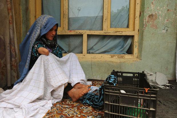 Pari tricota usando os pés em sua casa em Herat (Foto: Aref Karimi/AFP)