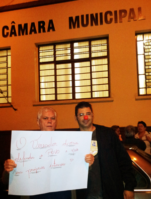 """Manifestante exibe placa que diz """"O vereador deveria defender o povo e não seus próprios interesses"""".  (Foto: Fotos Cedidas)"""