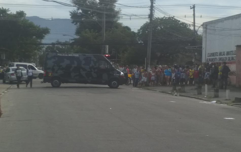 Curiosos olham de longe a ação da polícia na perícia e retirada do corpo do traficante encontrado morto dentro de um carro.
