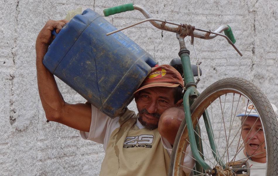 Homem equilibra bicicleta e tonel cheio de água nos ombros e cabeça, em Jutaí.