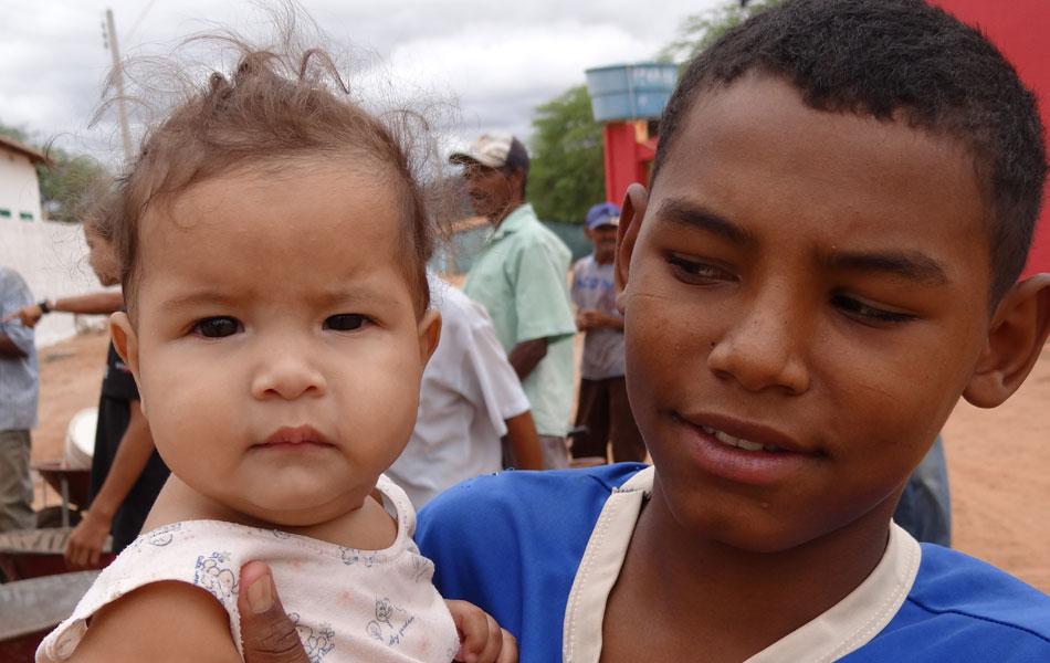 Menino carrega bebê no colo enquanto a mãe dela está na fila da água, em Jutaí.