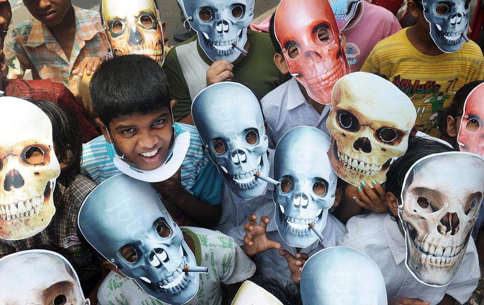 Crianças usam máscaras de caveira durante passeata em Kolkata, na Índia