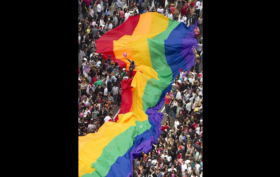 Bandeira colorida gigante é carregada durante o percurso da Parada Gay, na Avenida Paulista