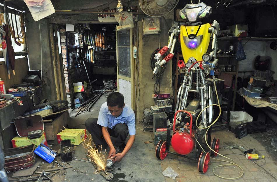 Chinês corta um componente para seu robô em sua oficina em Shenyang. Wu passou mais de 10 dias para fazer este robô de quase dois metros de altura usando peças de bicicletas elétricas abandonadas.