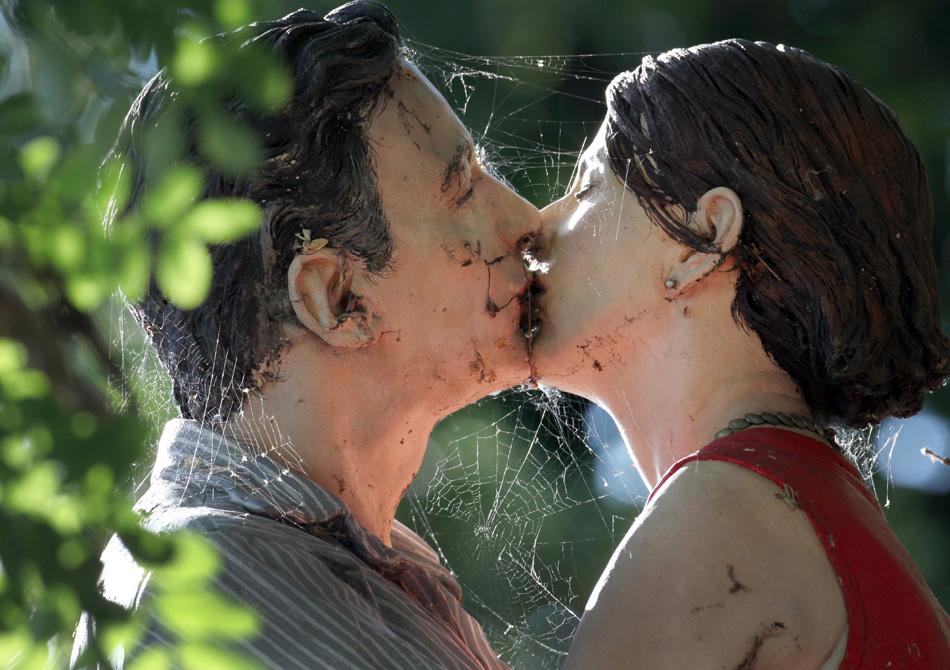 """Aranha envolve com sua teia uma escultura de um casal se beijando em Dusseldorf, oeste da Alemanha. A escultura faz parte da série """"Saeulenheilige"""" do artista alemão Christoph Poeggeler."""