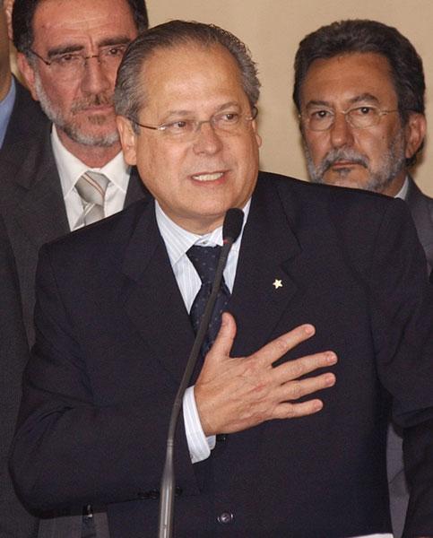 A denúncia do presidente do PTB envolve o então ministro-chefe da Casa Civil, José Dirceu, braço direito de Lula. Jefferson o aconselha a deixar o cargo ('Sai daí, Zé. Sai logo'), o que acaba se cumprindo dias depois. Na foto, Dirceu anuncia sua renúncia.