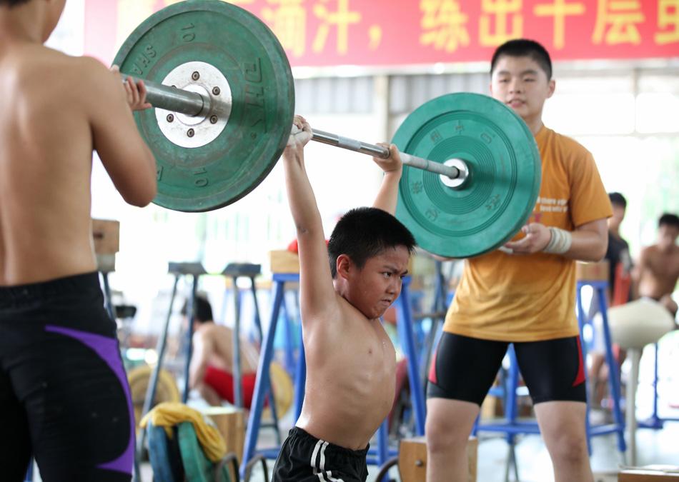 Chinês levanta peso em academia no sudeste da China.