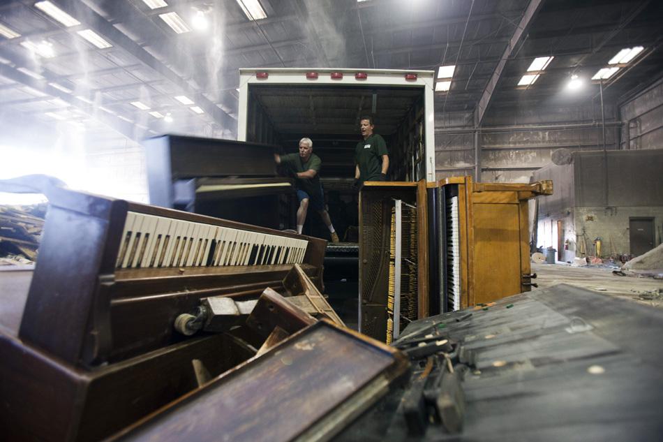 Homens descarregam pianos em um depósito de lixo em Southampton, na Filadélfia. Um século depois do pico de fabricação de piano nos EUA, o despejo é cada vez mais o destino final do instrumento.
