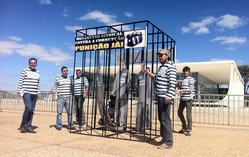 3 de agosto - Manifestantes montam 'cela' de cadeia com réus representados como presos em frente ao STF