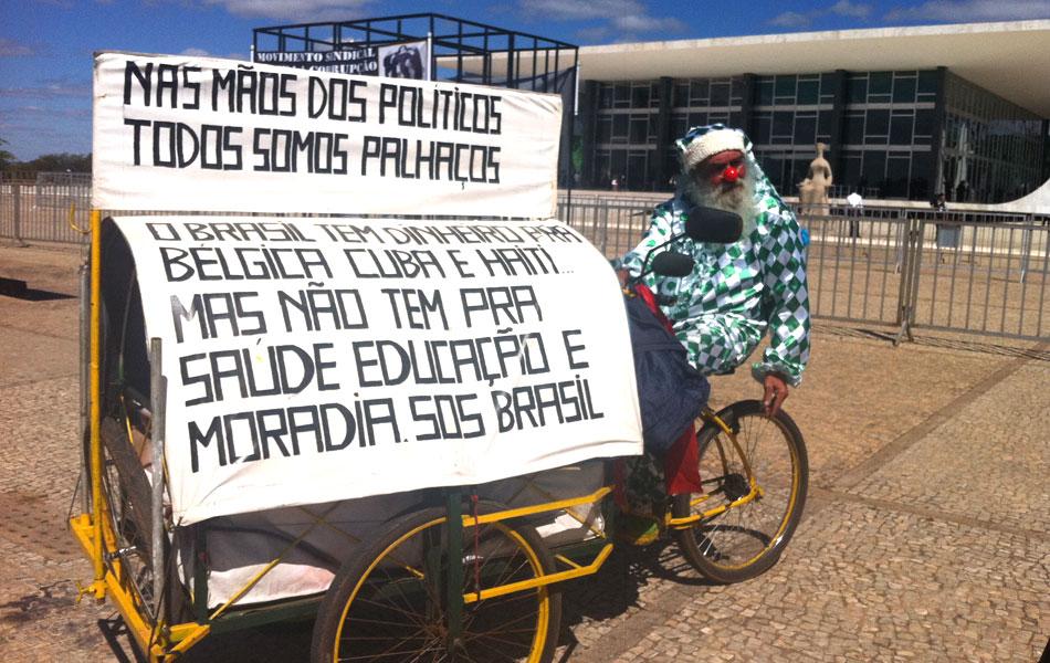 3 de agosto - De triciclo, Nilson exibe faixa grande com mensagem aos políticos, colocada sobre o triciclo que ele usa como moradia