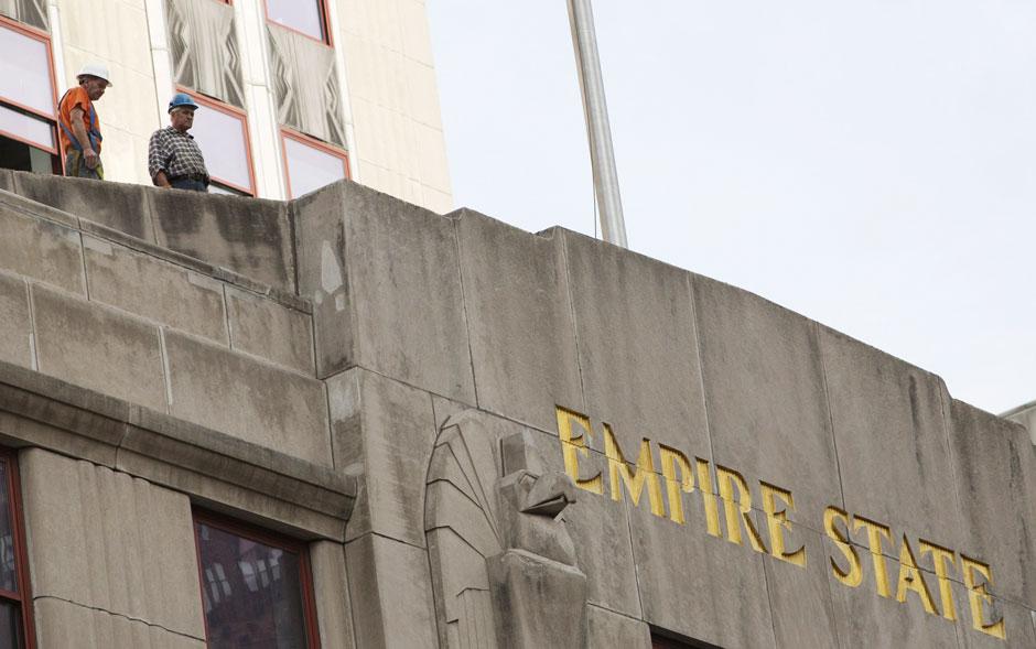 Operários observam o local de cima do teto do edifício Empire State