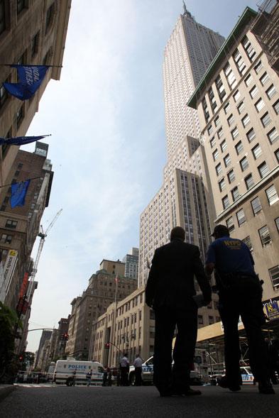 Policiais caminham nas proximidades do edifício Empire State, visto ao fundo