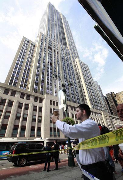 Passantes observam e fotografam a cena do crime em frente ao popular ponto turístico de Nova York