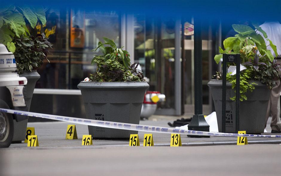 Placas de evidência indicam cartuchos de bala próximos a um corpo coberto