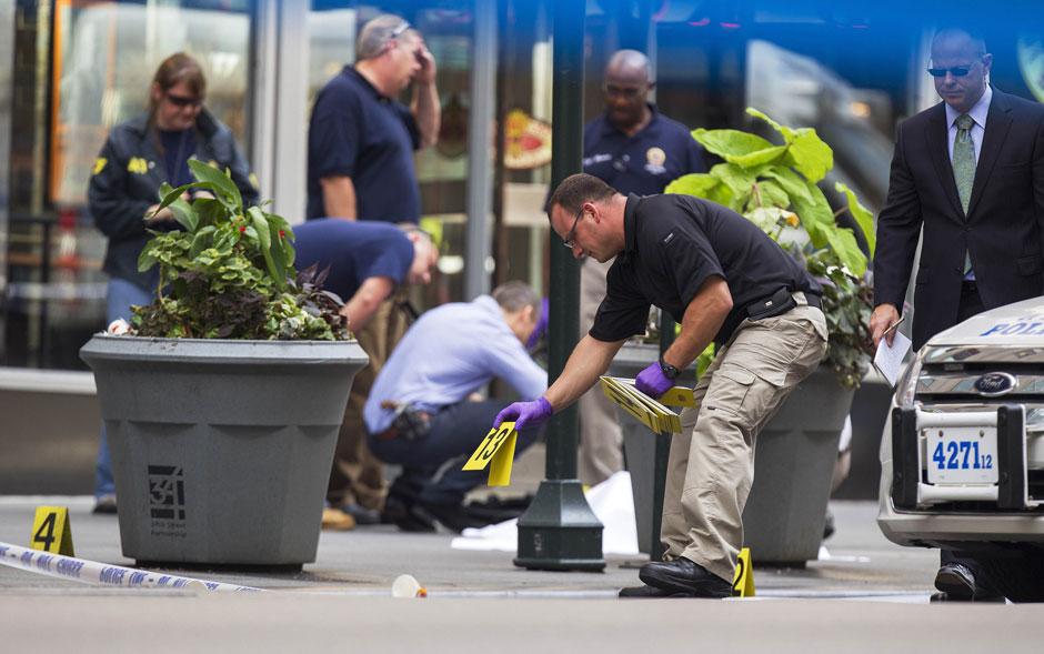 Placas de evidência indicam cartuchos de bala próximos a um corpo