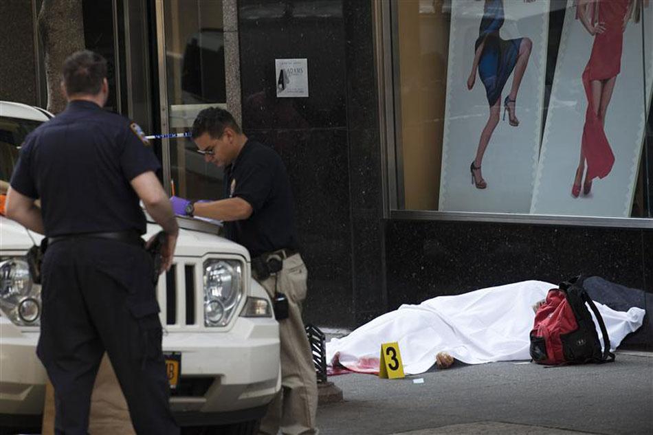 Detetives da Polícia de Nova York examinam local ao lado do corpo de suposto atirador que abriu fogo contra transeuntes em frente ao edifício Empire State Building, em Nova York.