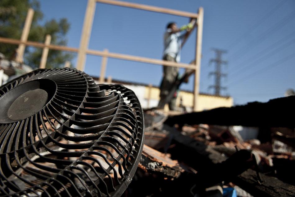 Moradores da favela do Areão, atingida por um incêndio na última sexta-feira, limpam o terreno devastado pelo fogo e reerguem os alicerces das novas casas.