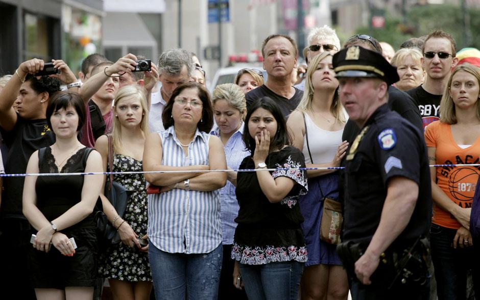 Multidão observa a cena do tiroteio e aguarda novidades da polícia. Segundo as autoridades, um ex-funcionário 'descontente' matou um ex-colega de trabalho a tiros