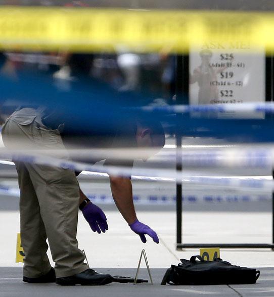 Policial inspeciona provas demarcadas na cena do tiroteio