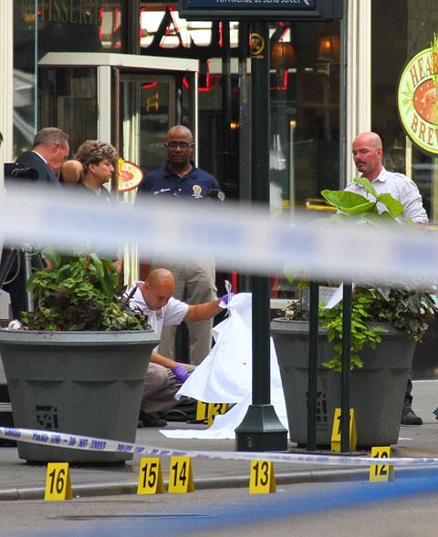 Policial inspeciona um corpo coberto