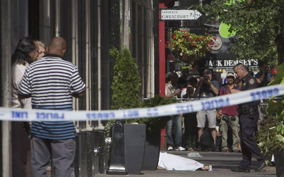 Corpo é visto coberto em área do tiroteio isolada pela polícia em frente ao Empire State Building, em Manhattan