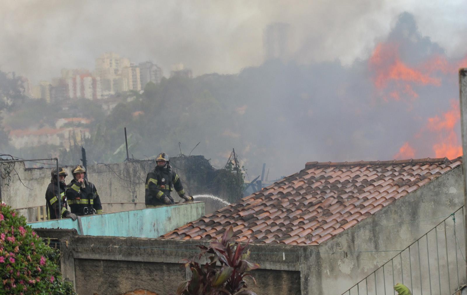 Da laje de uma casa, bombeiros tentam combater fogo