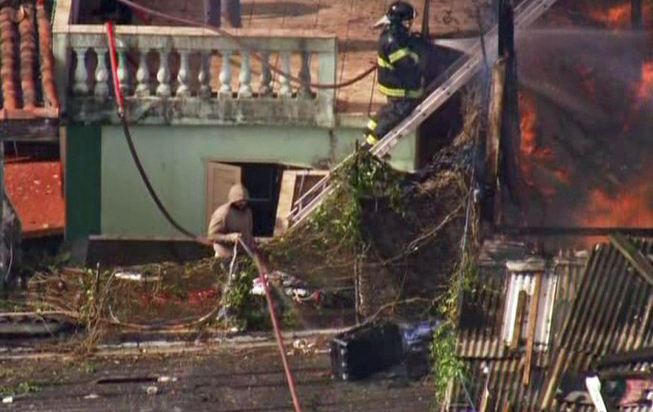 Bombeiros utilizam escadas para tentar conter o avanço das chamas